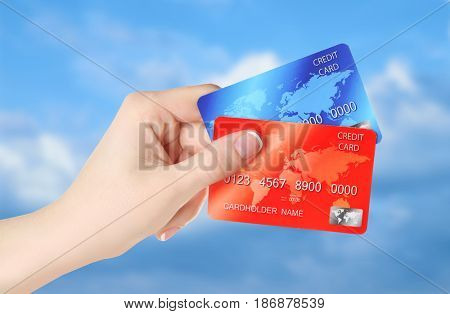 Travel concept. Woman holding credit cards on sky background
