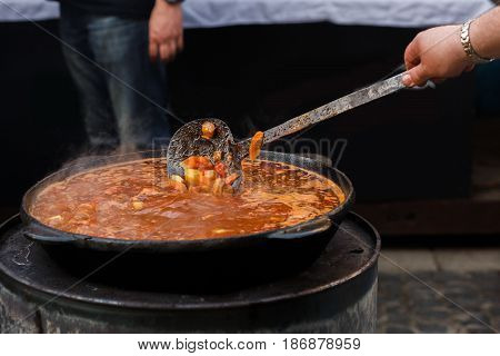Delicious Goulash In Big Bowl With Spoon On Open Grill, Outdoor Kitchen. Chef Making Yummy Hungarian