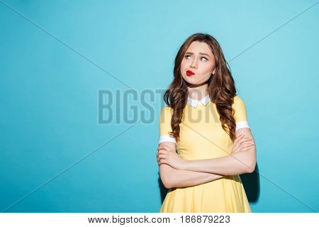 Portrait of a disappointed cute girl in dress standing with arms folded and looking away isolated over blue background