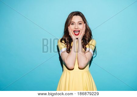 Portrait of a happy excited woman in dress with open mouth keeping hands at her face isolated over blue background