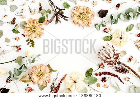 Round frame wreath with dried flowers: beige peony protea eucalyptus branches roses on white background. Flat lay top view. Floral background