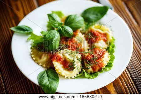 Ravioli with tomato sauce on a wooden table