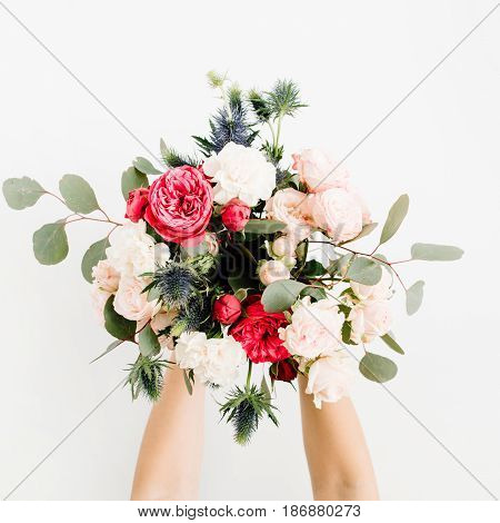 Girl's hands holding beautiful flowers bouquet: bombastic roses blue eringium eucalyptus isolated on white background. Flat lay top view. Floral composition