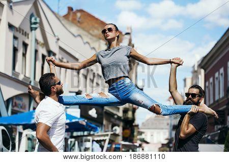 leg split of young woman in street training sport in city outdoor on hands of men