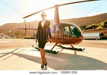 Elegant business woman near the helicopter. Business success and luxury concept