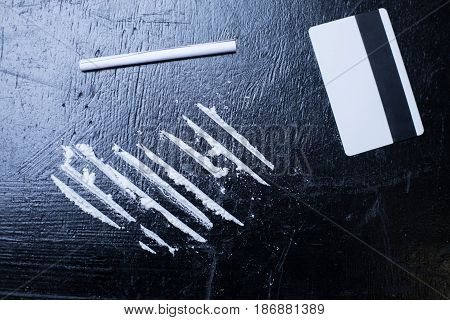 White lines of pleasure for freaks. White straight long cocaine lines located on the table in the darkness next to the credit card