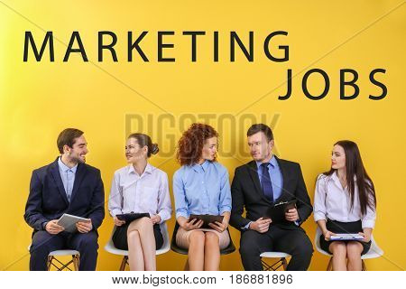 Marketing jobs concept. People waiting for interview on color wall background