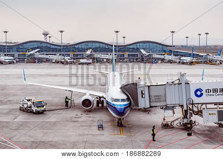 Urumqi China October 28 2016: Plane to Chengdu stands by the terminal in the city airport at early morning time.