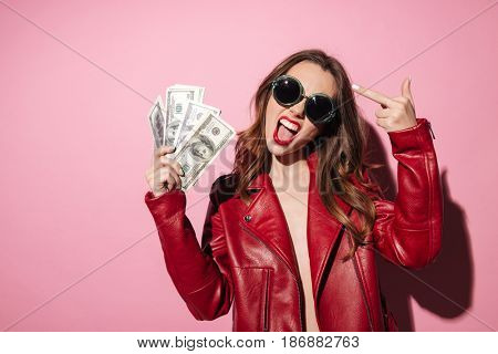 Portrait of an arrogant crazy girl in leather jacket holding money banknotes and showing middle finger gesture isolated over pink