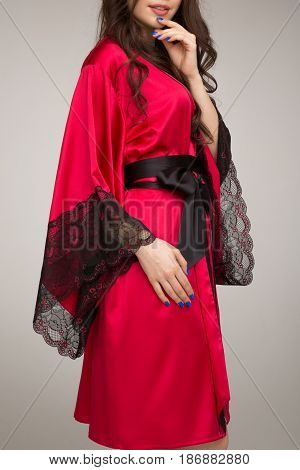 Girl in red silk robe, on gray background