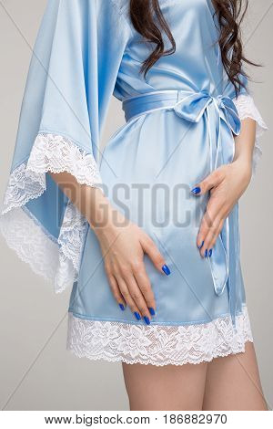 Girl in blue silk robe, on gray background