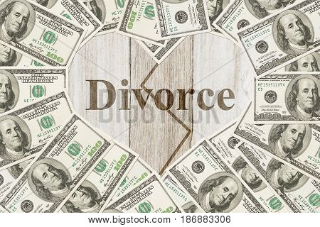Money and divorce message One hundred dollar bill in the shape of a heart with a weathered wood heart with text Divorce
