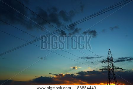 Power lines against the sky at sunset or at sunrise