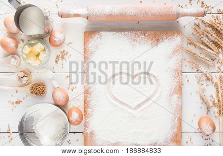 Love baking background. Cooking ingredients for yeast dough and pastry, eggs, butter and board sprinkled with flour, top view