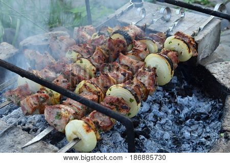 Barbecue Marinated Meat With Onion And Bacon. Shashlik Or Shish Kebab Preparing On Grill Over Charco