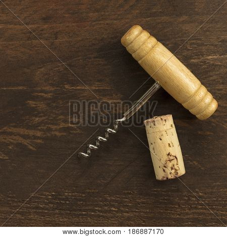 A photo of an old-fashioned corkscrew with a cork, shot from above on a dark wooden background texture with plenty of copy space. A square design template for a wine list or a tasting invitation