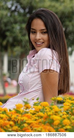 A Female Teen Sitting Among A Flower Garden