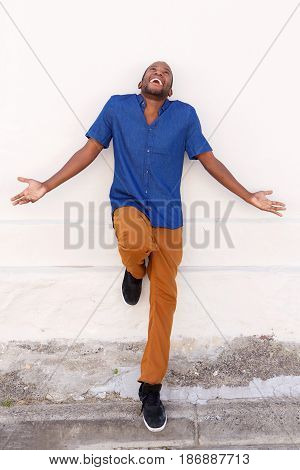 Smiling African Man Looking Up With His Arms Outstretched