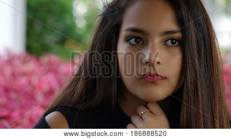 Serious Hispanic Teen Girl with Purple Flowers