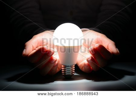 Female Hands Holding A Glowing Led Bulb In The Dark