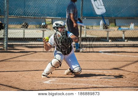 Teenage softball catcher ready to throw the ball.