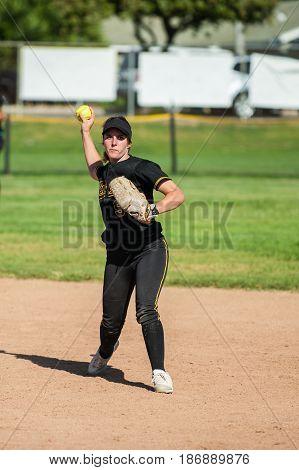 Teenage softball infielder ready to throw the ball.