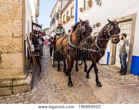 OBIDOS PORTUGAL - APRIL 03 2017: People riding in horse cart on the main street of Obidos on April 03 2017.