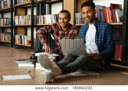 Picture of young two african men students sitting in library reading books using laptop computer. Looking at camera.