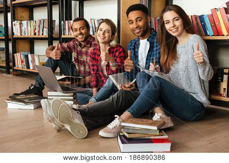 Picture of young smiling students sitting in library on floor showing thumbs up. Looking at camera.