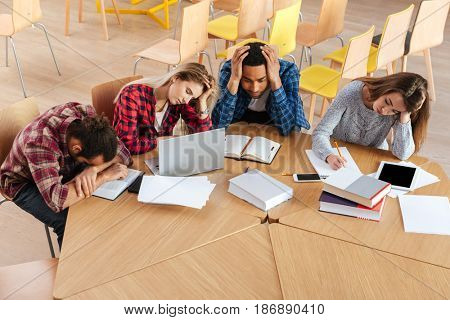 Picture of young tired students sitting in library. Looking aside while using laptop computer and reading books writing notes.
