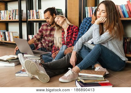 Picture of young tired students sitting in library on floor using laptop computer and reading books. Looking aside.