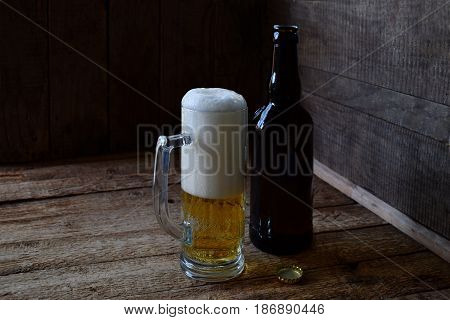 Mug Of Beer, Bottle On Wooden Background. Photographed With Natural Light