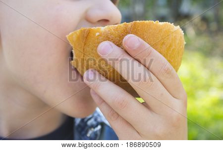 Child eating slice of bread. a boy bites bread crust. hunger