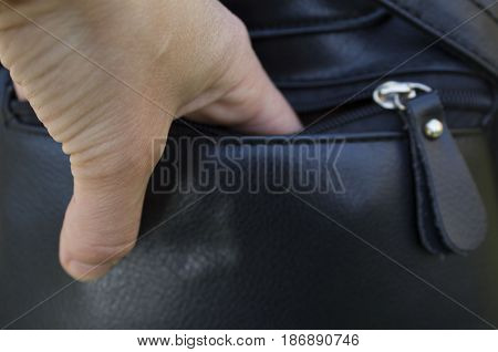 A Person Stealing Purse From Handbag. Leather bag with zipper. thief's arm.
