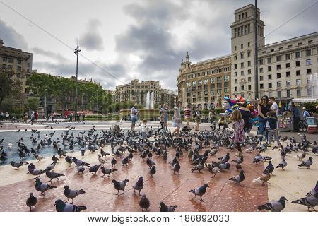 Barcelona, May 07, 2017: People feeding the pigeons in Placa de Catalunya near La Rambla. Barcelona is the most visited city in Spain