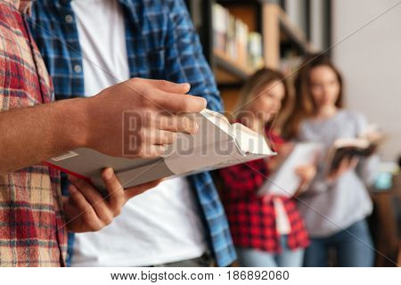 Close up portrait of a group of students holding books while standing at the bookshelf in library