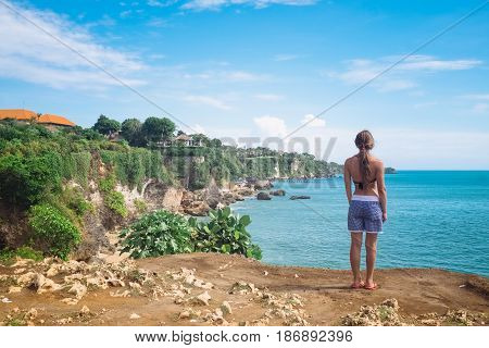 Woman stands on on the top of mountain peak with sea view and enjoy the beautiful landscape, travel concept, Bali island, Indonesia. Freedom and happiness, beautiful young girl over sea shoreline