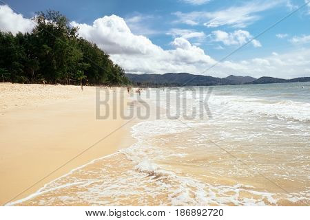 Tropical beach scenery at Andaman sea in Phuket, Thailand. Exotic sea view with people relaxing on vacation at tropical summer paradise beach of Phuket island with sunny sky and clouds on horizon