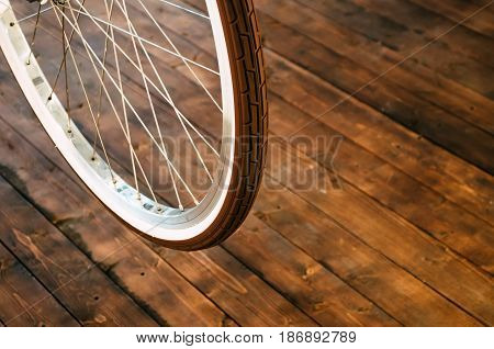Wheel of a stylish bicycle with a white rim and a brown rubber tire on a stylish wooden background