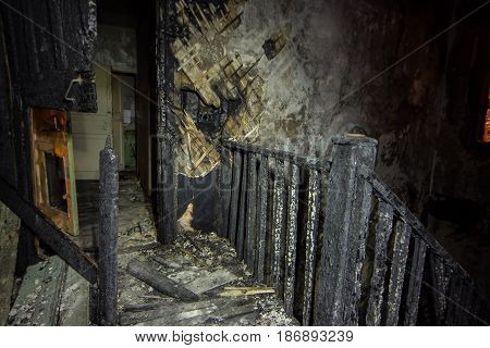 Interior of the burned by fire house, burned wooden stairs.