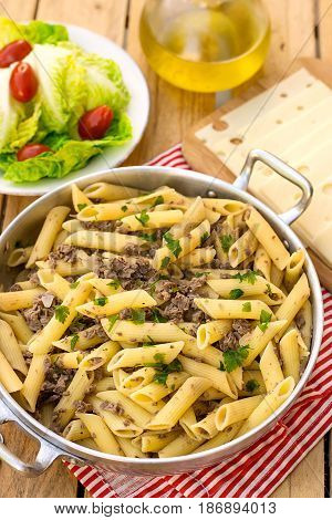 Pasta penne rigate with ground meat parsley and onions in a pan