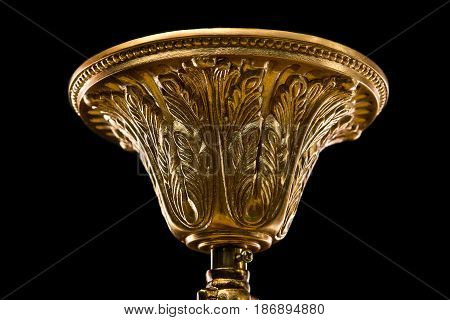 Top cap of chandelier. Contemporary gold chandelier isolated on black background. close-up detail . Crystal chandelier