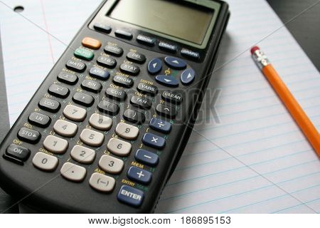 A graphing calculator with a piece lined paper.