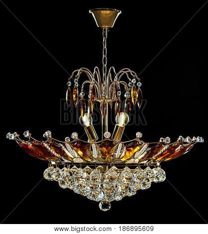 Contemporary gold chandelier isolated on black background. Crystal chandelier decorated amber crystals