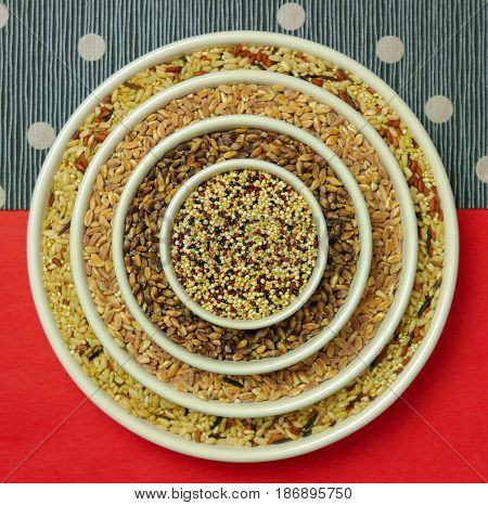 Whole grains in a concentric circle pattern in white bowls on red and blue striped paper with silver dots