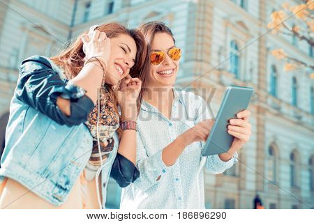 Two young beautiful girls are walking through the city and listening to music.