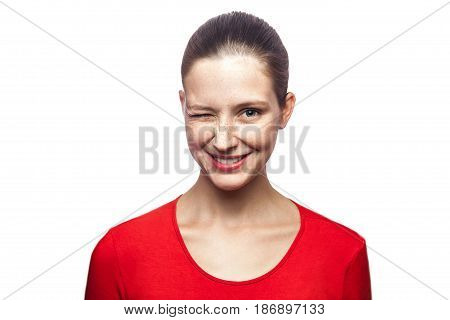 Portrait of funny positive winking woman in red t-shirt with freckles. looking at camera with toothy smile studio shot. isolated on white background.