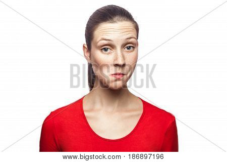 I don't know. portrait of funny confused woman in red t-shirt with freckles. looking at camera studio shot. isolated on white background.