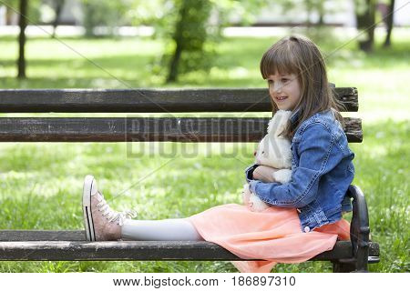 Little Beautiful Girl Sitting On A Park Bench And Holding Her Favorite Stuffed Toy