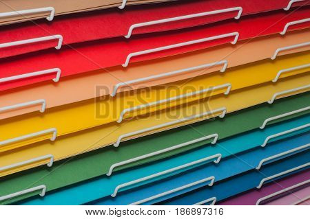 Sheets of colored cardboard for designer creative works. Stacks on a display paper rack, close-up